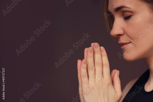 Fototapeta middle aged woman meditating with her eyes closed, practicing Yoga with hands in prayer position