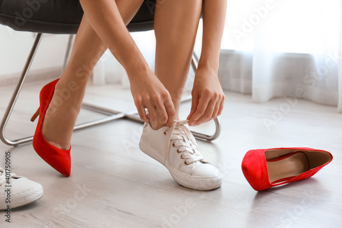 Carta da parati Woman taking off uncomfortable shoes and putting on sneakers in office, closeup