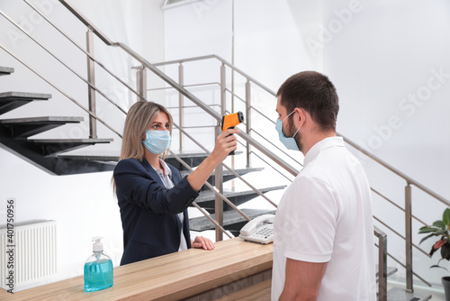 Woman in mask measuring temperature of employee with noncontact thermometer at office reception