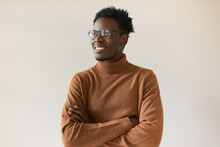 Studio Shot Of Handsome Enthusiastic Dark Skinned Guy In Trendy Eyeglasses Having Inspired Facial Expression, Thinking About Future, Making Plans, Keeping Arms Crossed On His Chest And Smiling
