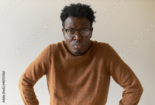 Fotografie, Obraz Studio image of frustrated displeased young Afro American man in stylish glasses frowning having serious strict facial expression, being dissatisfied of bad work results