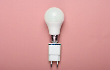 Smart Energy-saving Light Bulb With A Charger On Pink Background. Top View