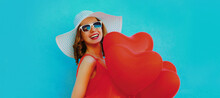 Portrait Of Beautiful Happy Laughing Woman With Bunch Of Red Heart Shaped Balloons Wearing A Summer Straw Hat And Sunglasses On A Blue Background