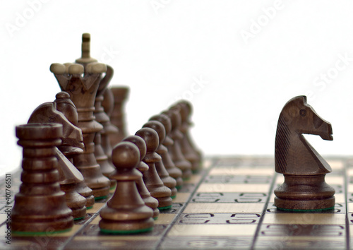 Black chess set with a forward placed knight horse on top of a chess board in fr Fototapete