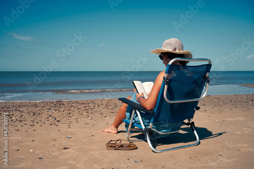 Tablou Canvas A female in a sunbed spending the leisure time on the beach reading a book