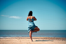 A Female In A Summer Dress Doing Yoga Exercise On The Sandy Beach