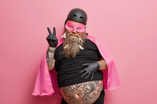 Portrait Of Funny Bearded Superhero Makes Peace Gesture Has Big Tattooed Belly Wears Mask Helmet And Cape Isolated Over Pink Background. European Adult Man Shows Victory Sign Being On Costume Party