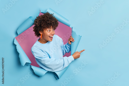 Cheerful dark skinned woman with curly hair dressed in casual sweater indicates at copy space shows amazing offer breaks through paper background expresses positive emotions. Your advertisement there