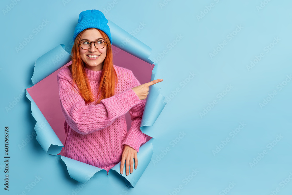 Leinwandbild Motiv - Wayhome Studio : Pretty smiling redhead woman in blue hat and knitted sweater points away on blank space advertises promo being in good mood poses through paper background. Look at this nice offer. Your advert here