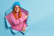 Leinwandbild Motiv Pretty smiling redhead woman in blue hat and knitted sweater points away on blank space advertises promo being in good mood poses through paper background. Look at this nice offer. Your advert here