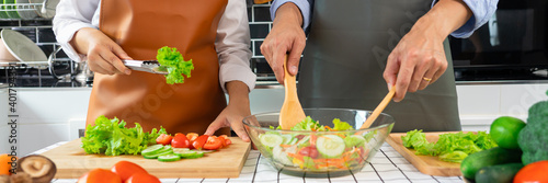 Fotografia Happy couple having fun standing in kitchen at home preparing vegetable salad husband and wife vegetarians chop vegetables prepare for dinner in loft kitchen at home