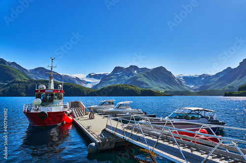 Svartisen glacier and its sourrounding moutains in the background and in the foreground a boat jetty with a big red boat