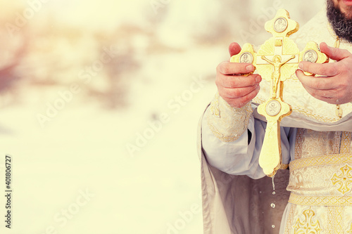 Tablou Canvas The hands of a priest dip an Orthodox gold cross into the river