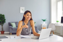 Smiling Asian Woman Office Worker Working In Modern Spacious Office With Laptop