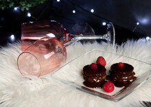 Chocolate Brownies With Melted Hot Chocolate Topping And Berries Decoration. Two Pink Wine Glasses. Hygge. Selective Focus Background Bokeh