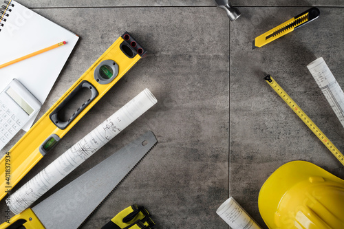 Fototapeta Contractor concept. Tool kit of the contractor: yellow hardhat, libella, hand saw. Plans and notebook on the gray tiles background. obraz na płótnie