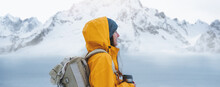 Alone Brave Woman Traveler With Backpack Looking Away To Winter Mountains. Female Explorer Wearing Rucksack Among Winter Landscape Travel At Holidays Journey. Wide Shot