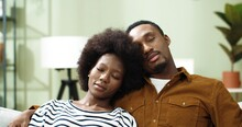 Camera Approaching African American Cute Happy Family Couple Resting On Sofa In Cozy Room Embracing, Hugging With Calm Faces And Closed Eyes. Close Up Of Wife And Husband Having A Nap
