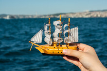 A Closeup Shot Of A Person Holding A Boat Toy With The Sea In The Background