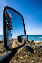 Roadtrip With The Campervan Showing Surfboards In The Outside Mirror, With A Beautiful Blue Ocean With Waves In The Background. Outdoor Lifestyle.