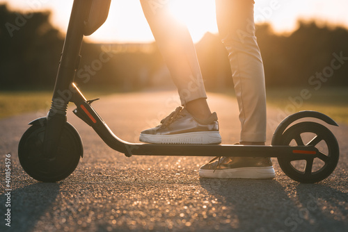 Fotografiet Close up of woman riding electric kick scooter at sunset