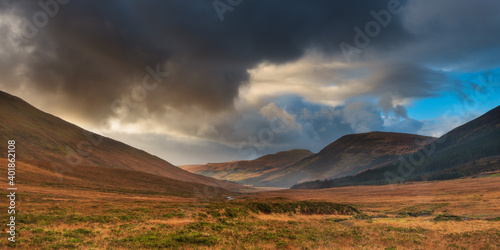 Fototapeta sunset over the mountains with dark clouds on one side in Scotland Isle of Skye