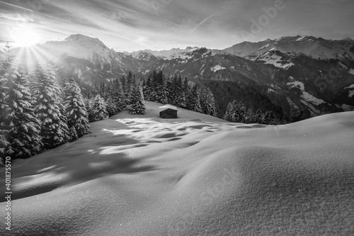 Skihütte auf einer Waldlichtung in den verschneiten Bergen von Österreich in schwarz weiß