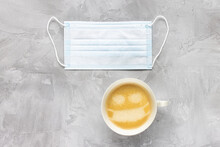 White Medical Mouth Mask And Cup Of Coffee With Foam Shape Of Face With Mask Over Mouth, Gray Background. Cafeteria Restrictions And Quarantine During Coronavirus Covid-19 Concept. Flat Lay Copy Space