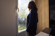 An attractive female standing in a room by a window