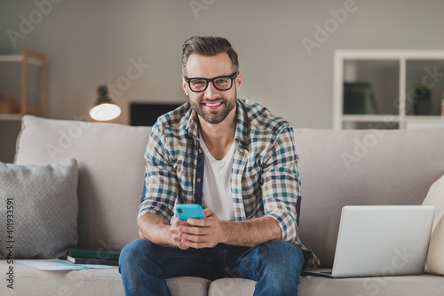 Fototapeta Photo of young cheerful handsome man happy positive smile sit sofa indoors chat type sms browse cellphone obraz