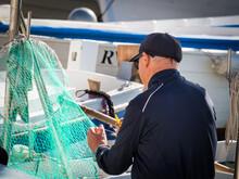 Fisherman Repairs His Net At Rovinj Croatia