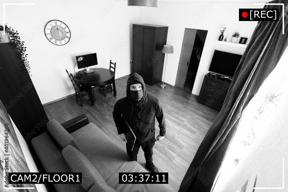 Fototapeta house robbery - burglar captured on surveillance security camera in living room