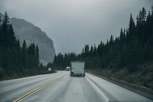 Road Trip With Car Driving In Pine Forest With Rocky Mountains On Gloomy At Banff National Park
