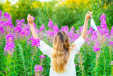 Fototapeta Zwierzęta - The girl who removed the medical mask from her face raised her hands up in a gesture of joy on a green summer background. End of quarantine concept