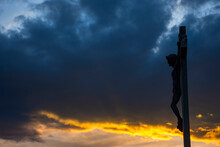 Jesus Christ On The Cross Against Dramatic Cloudy Sky, At Sunset. Crucifixion, Religion And Spirituality