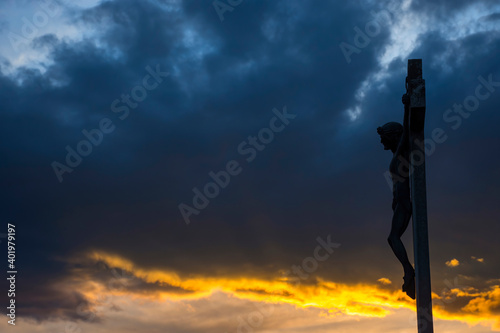 Canvas Print Jesus Christ on the cross against dramatic cloudy sky, at sunset