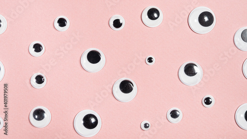 Fotografering panoramic background from pink paper with many flat plastic doll eyes
