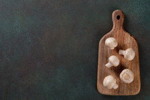 Champignon Mushrooms On Cutting Board Lying Over Dark Background With Copy Space. Top View.