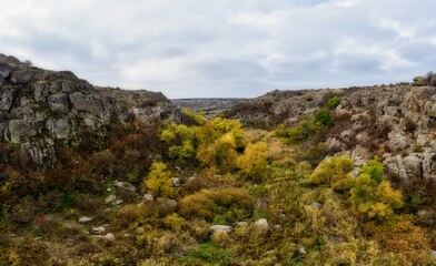 A picturesque stream flows in the Aktovsky Canyon, surrounded by autumn trees and large stone boulders