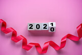Fototapeta Kawa jest smaczna - Flipping of wooden cubes block to change 2020 to 2021 year with ribbon on pink background. Merry Christmas and happy new year concept.
