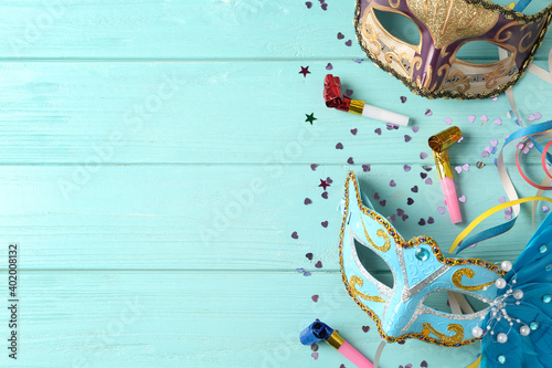 Foto Beautiful carnival masks and party decor on light blue wooden background, flat lay