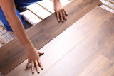 Fototapeta Kawa jest smaczna - Worker installing new wooden laminate over underfloor heating system, closeup