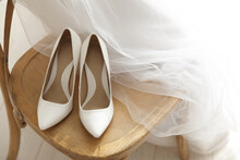 Pair Of White Wedding High Heel Shoes And Veil On Wooden Chair Indoors