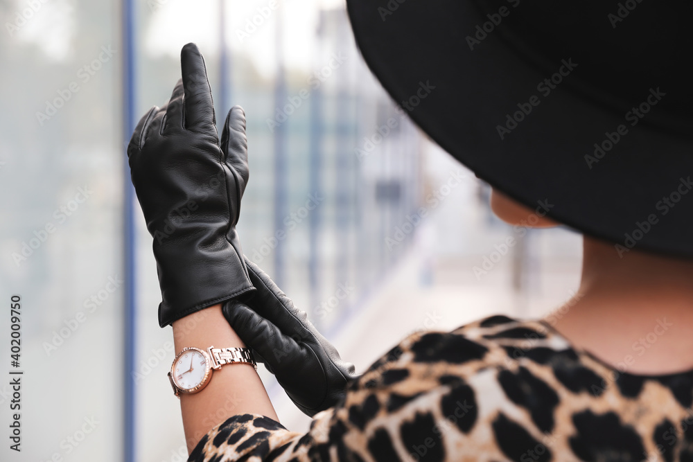 Fototapeta Young woman putting on stylish black leather gloves outdoors, closeup
