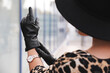 Young woman putting on stylish black leather gloves outdoors, closeup
