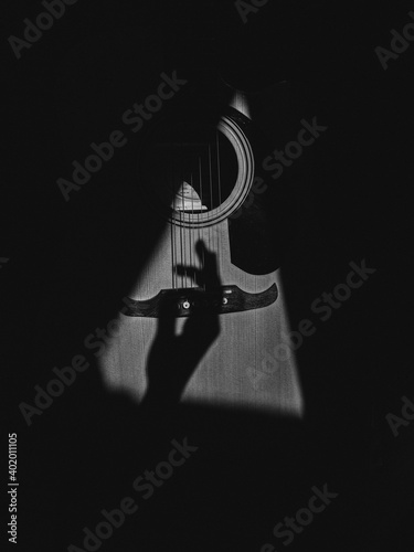 Fotografija A grayscale shot of hand shadow strumming on guitar strings