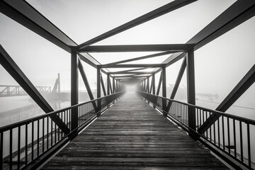 A grayscale shot of light at the end of a modern beautifully architectured bridge surrounded by fog