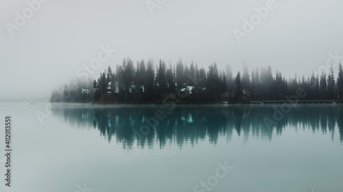 Photo A tiny kayak and water reflections of the peninsula of Emerald Lake surrounded by towering pine trees and thick eerie fog in Yoho National Park, BC, Canada