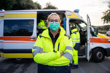 Portrait Of Young Millennial Woman With Arms Crossed At First Aid In Front His Colleagues In Ambulance At Break Time At Pandemic Time From Coronavirus, Covid-19 He Wearing Face Mask And Uniform Work
