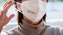 Corona Schutzmaske / FFP2 Atemschutzmaske / Frau / Maske Aufsetzen / Freizeit